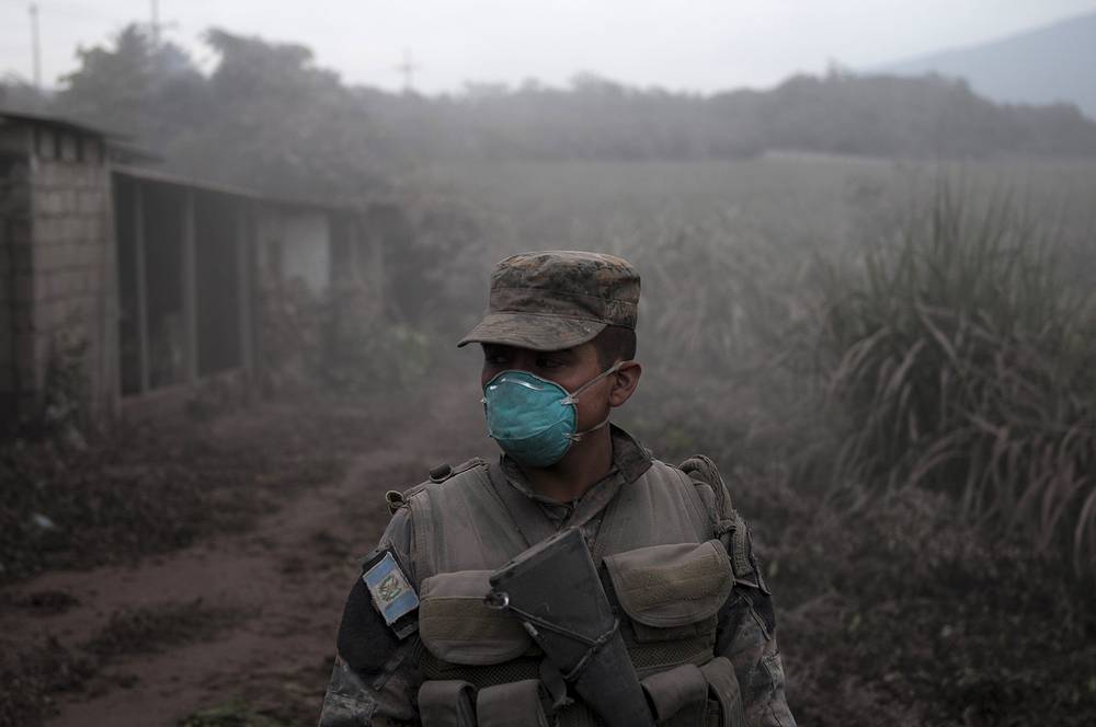 A soldier stands guard at a search and rescue site near the Volcan de Fuego in Guatemala