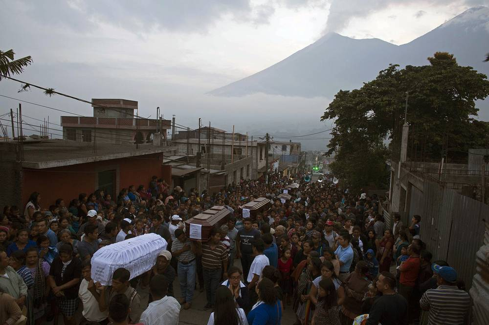 One of Central America's most active volcanos erupted in fiery explosions of ash and molten rock on June 3, killing people and injuring many others. Photo: People carry the coffins of seven people who died during the eruption of the Volcan de Fuego to the cemetery in San Juan Alotenango, Guatemala