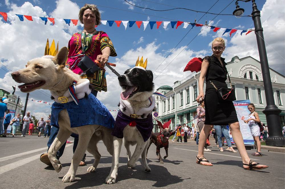 A woman with dogs takes part in a parade marking Russia Day, Omsk, June 12