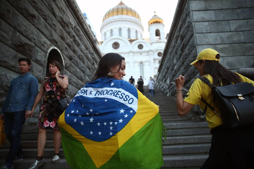 A football fan wrapped in a Brazilian national flag near the Christ the Saviour Cathedral in Moscow