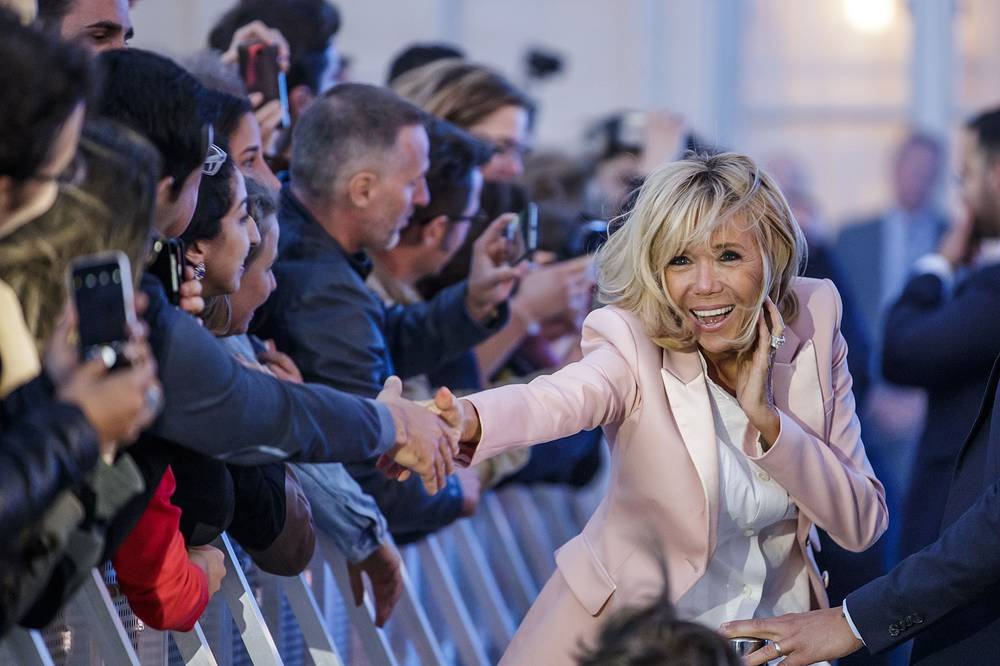 French President's wife Brigitte Macron greets people during the 'Fete de la Musique', the music day celebration in the courtyard of the Elysee Palace in Paris, June 21