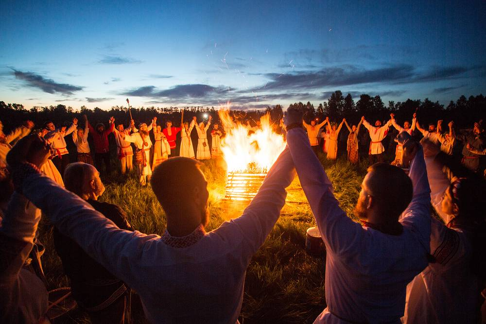 People gather round a bonfire during a summer solstice celebration in Omsk region