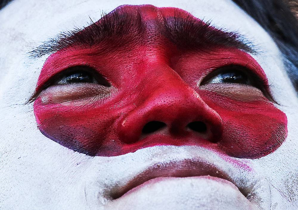 Japan's supporter with his face painted in the colours of the Japanese national flag watches group H match between Japan and Senegal. The game ended in a 2-2 draw