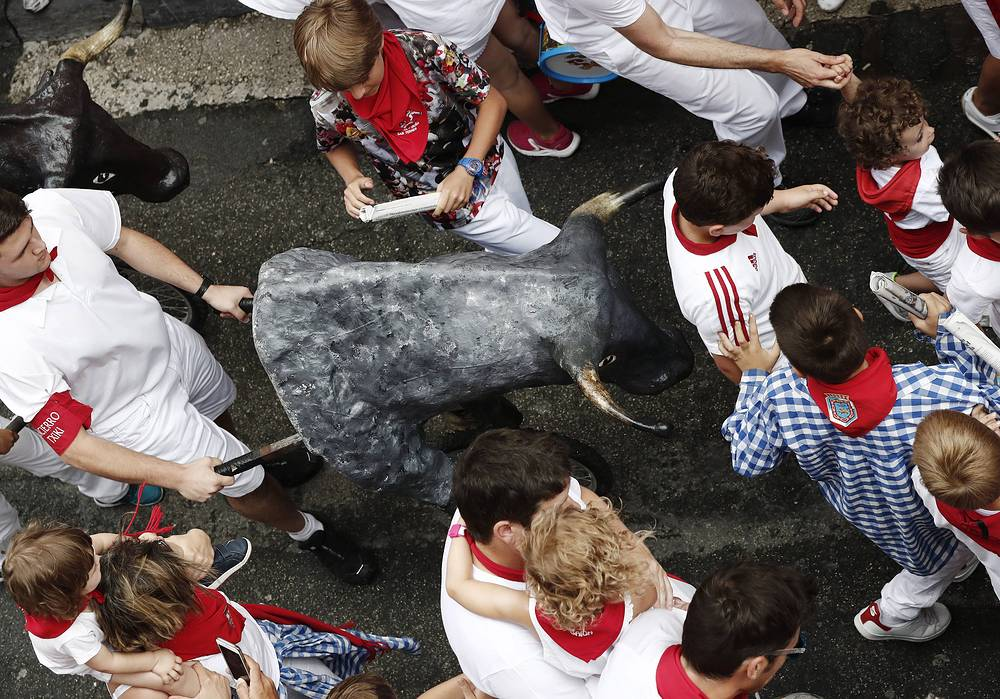 Children enjoy the traditional 'txiki' run (a San Fermin Bull Run for kids) in Pamplona