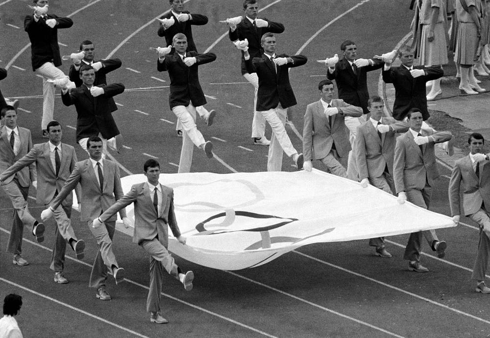 Soviet youth marching with the Olympic banner while others are carrying pigeons to be released, during opening ceremony of the 22nd Summer Olympic Games, July 19, 1980