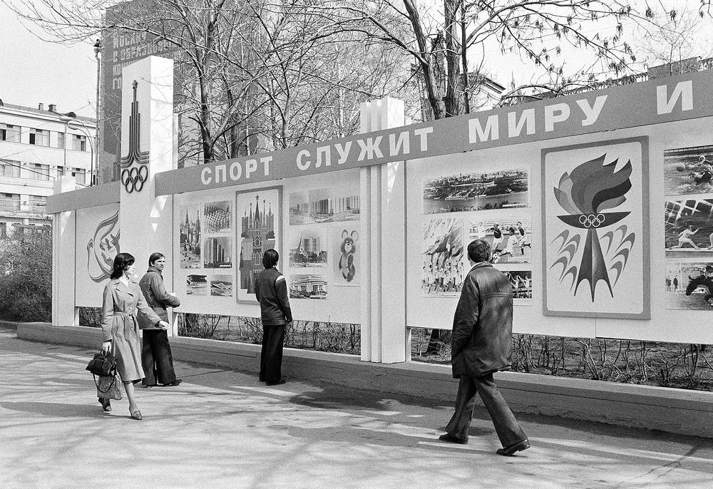 """Muscovites examine new Olympic billboard with sign reading """"Sport Serves Peace"""", erected after the United States announced it was boycotting the games"""
