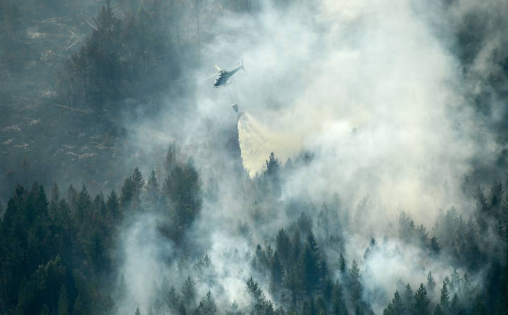 A firefighting helicopter drops water over the fire in Ljusdal, July 18
