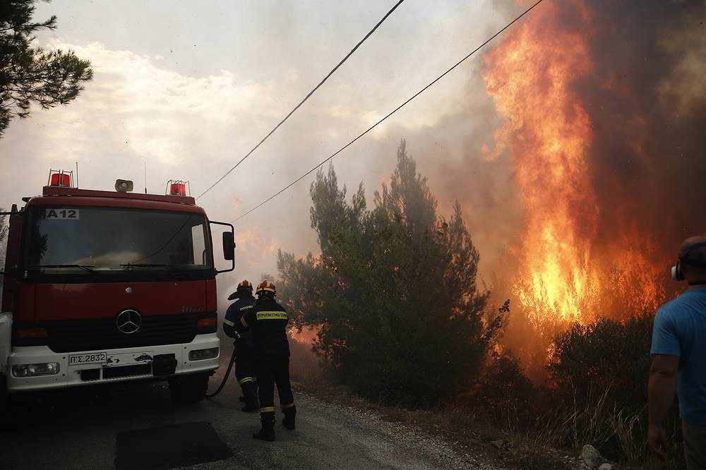 Firefighters trying to extinguish flames during a forest fire in Neo Voutsa, a northeast suburb of Athens