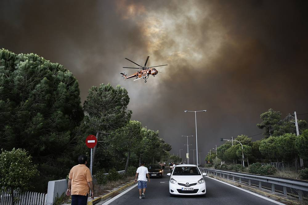 Two major forest fires were raging out of control on either side of the Greek capital on July 23, burning houses, prompting residents to flee and turning the sky over Athens a hazy orange from the smoke