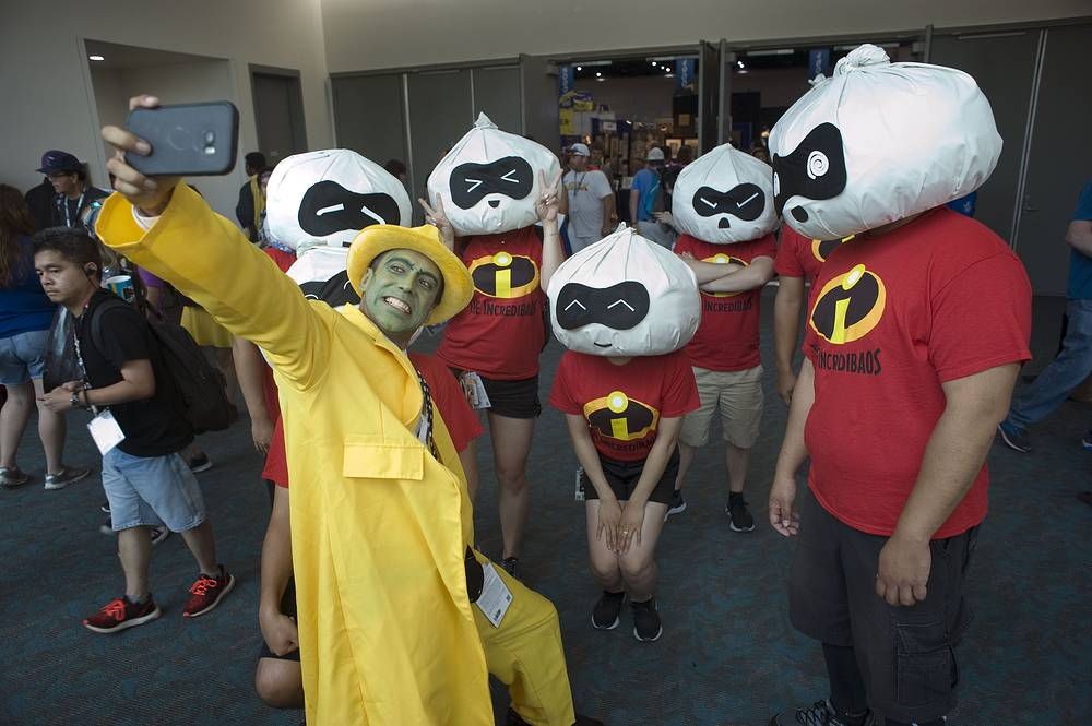 A man takes a photograph of himself with a group of people dressed as 'The Incredibles' at Comic Con International in San Diego, July 22