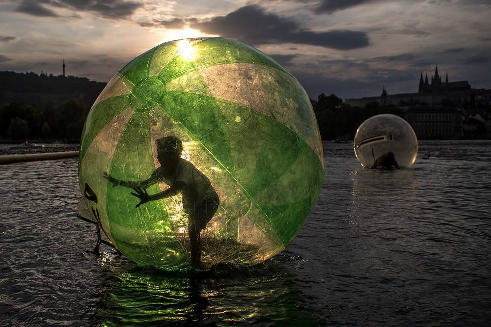 A boy plays inside a giant plastic ball, called a zorb, during a summer's day on the Vltava River in Prague, Czech Republic. A current heat wave brings temperatures of about 36 degrees Celsius across Czech Republic and many other parts of Europe