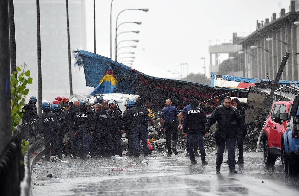 Police officers at the site of the collapsed bridge in Genoa