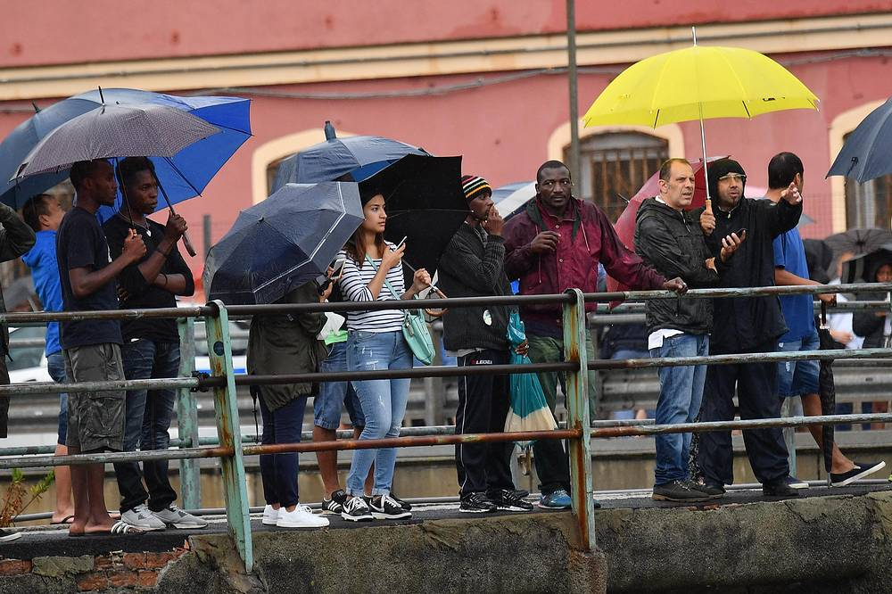 People look at the collapsed bridge in Genoa