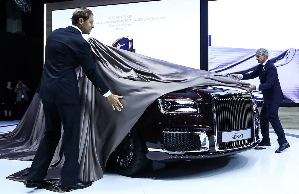 Russia's Industry and Trade Minister Denis Manturov and Aurus CEO Hilgert Franz Gerhard lifting the cover off an Aurus Senat vehicle at the 2018 Moscow International Motor Show