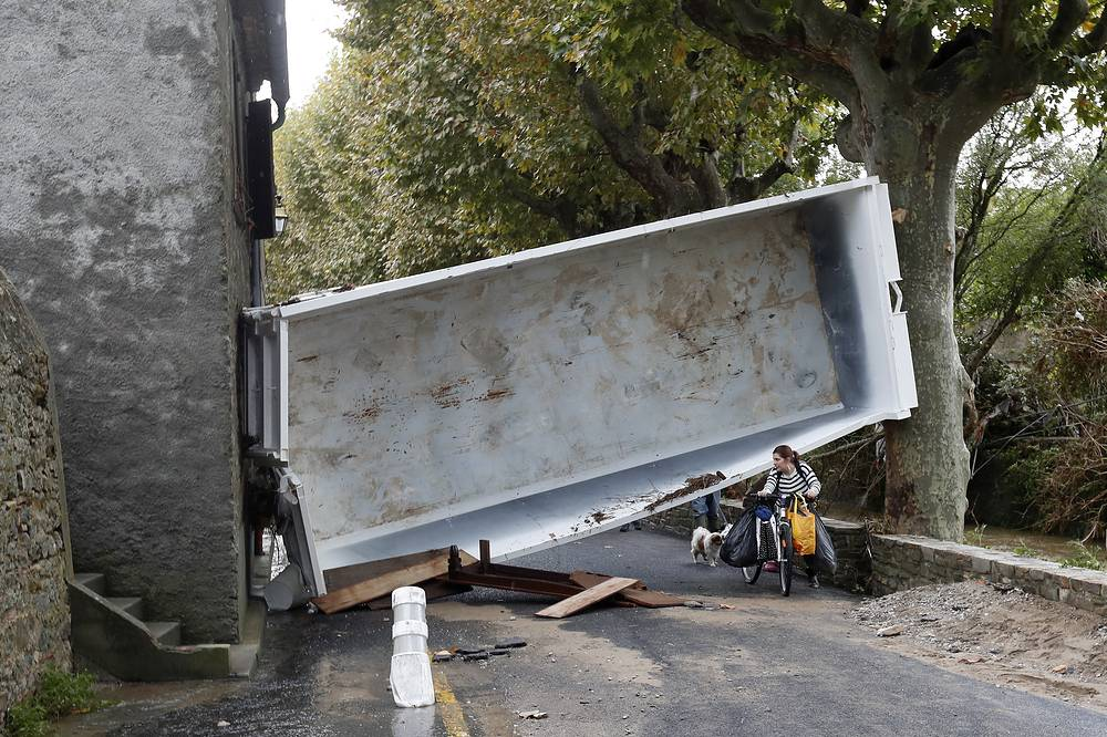 A woman passes under a dumpster in the middle of the street in Villegailhenc, France