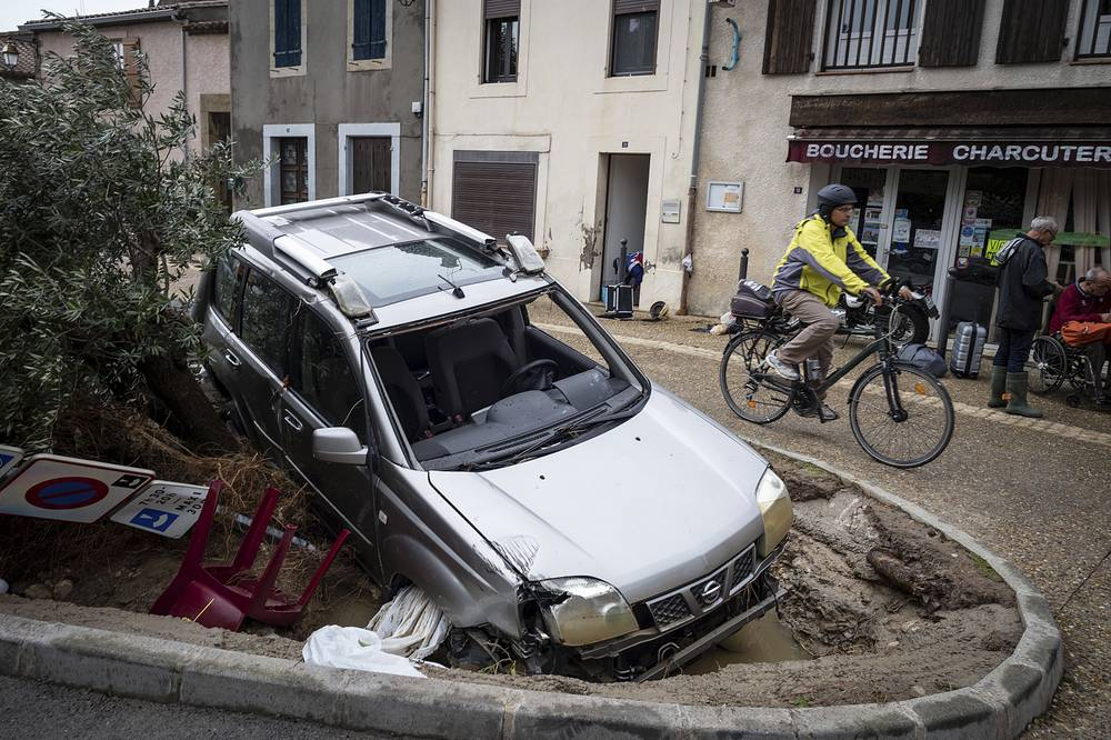 A man rides past a damaged car in the town of Villegailhenc, southern France