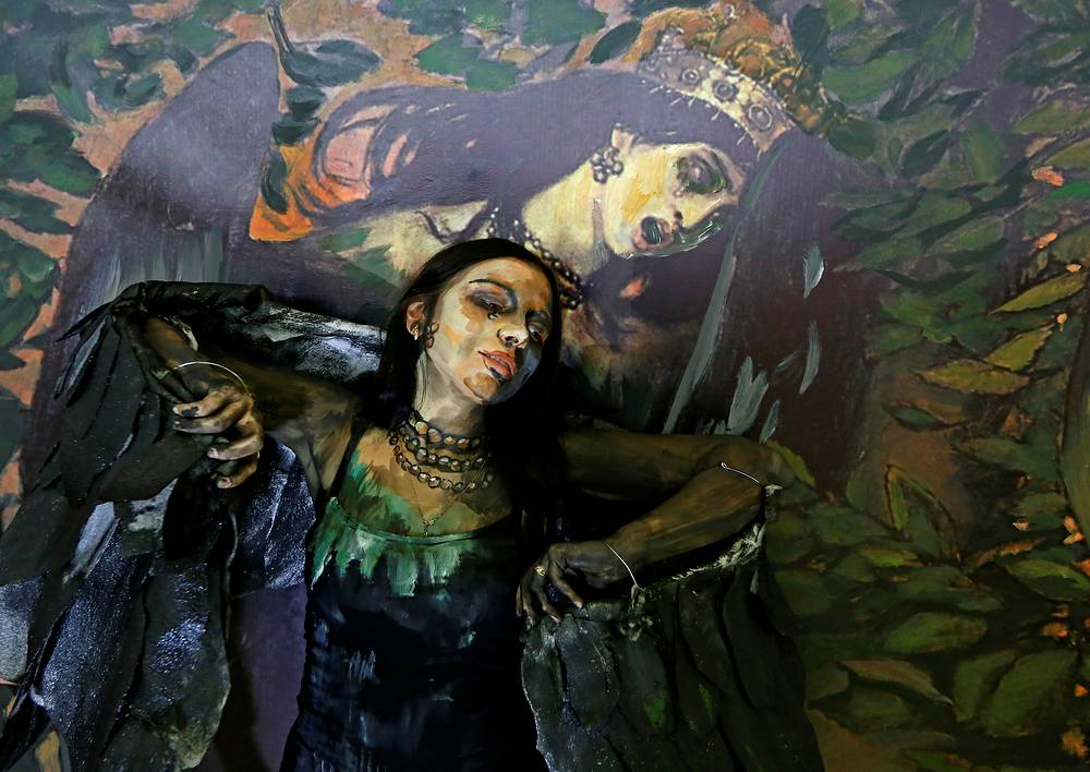 """Model poses while presenting a body art work by Russian artist Maria Gasanova from her """"The Alive Painting"""" series in front of a reproduction of Victor Vastensov's """"Sirin and Alkonost. A Song of Joy and Sorrow"""" during the Art Krasnoyarsk annual festival in Krasnoyarsk, October 24"""