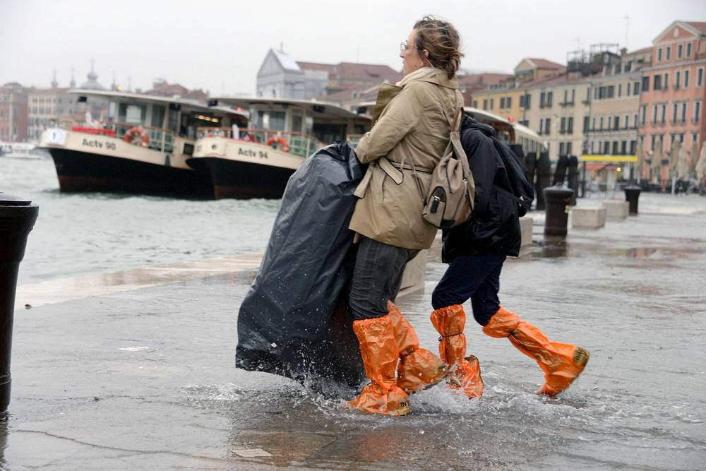 Tourists wander in high water in Venice