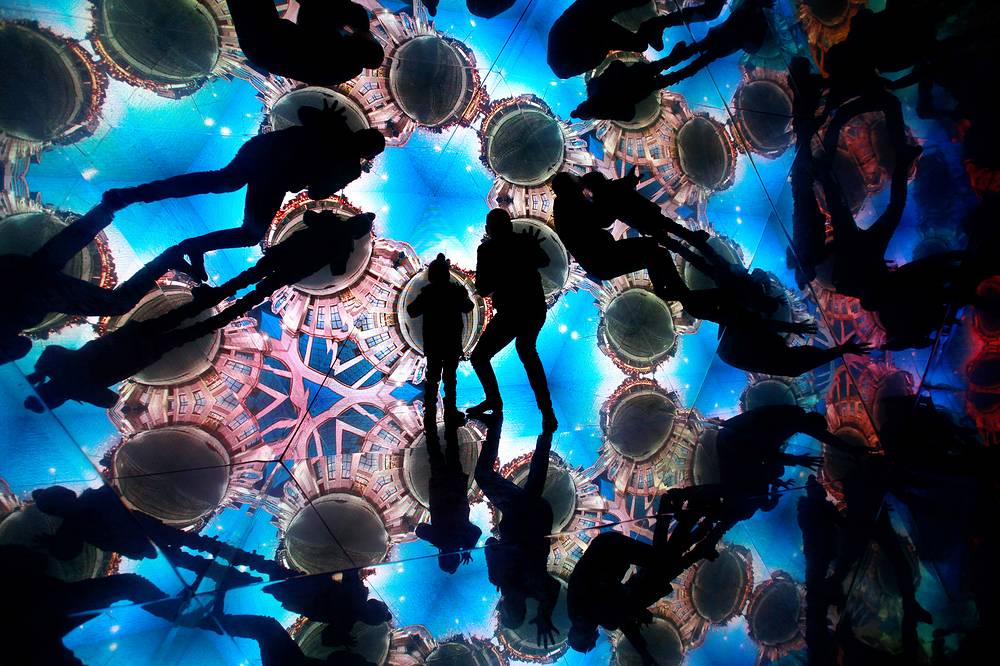People take part in the interactive object Kaleidoscope 'Time Machine' during the Light Festival Staro Riga in the Latvian capital of Riga, November 17