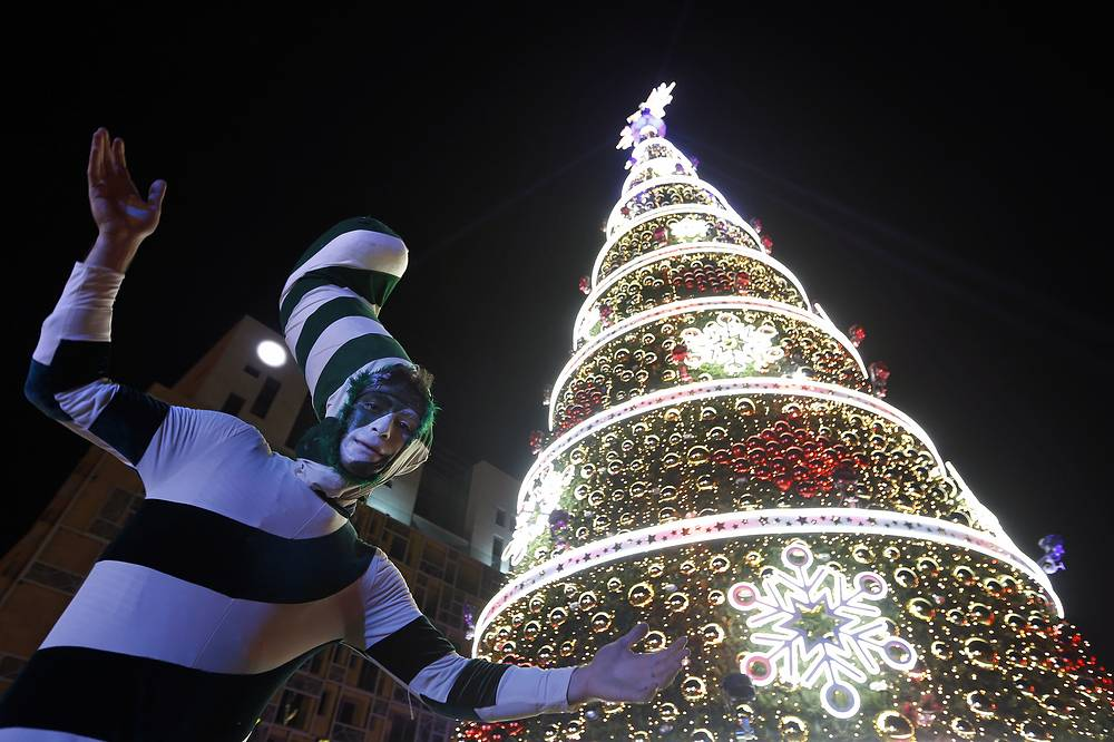 A man dressed in candy costume dances during the illumination of a giant Christmas tree in Beirut, Lebanon