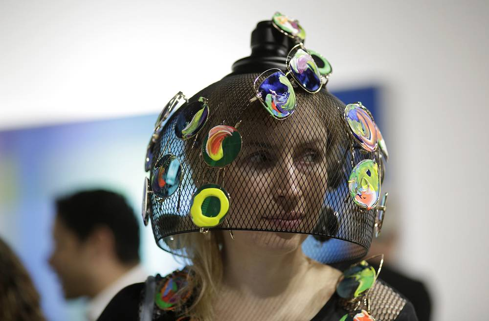 Artist Olga Kosheleva, of the Ukraine, wears a headpiece covered with painted sunglasses as she walks through Art Basel