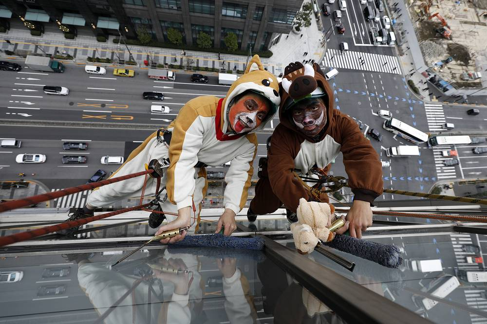 Window cleaners wearing a dog and a boar costumes clean windows of an hotel 55 meters above the street during an annual event in central Tokyo, December 13