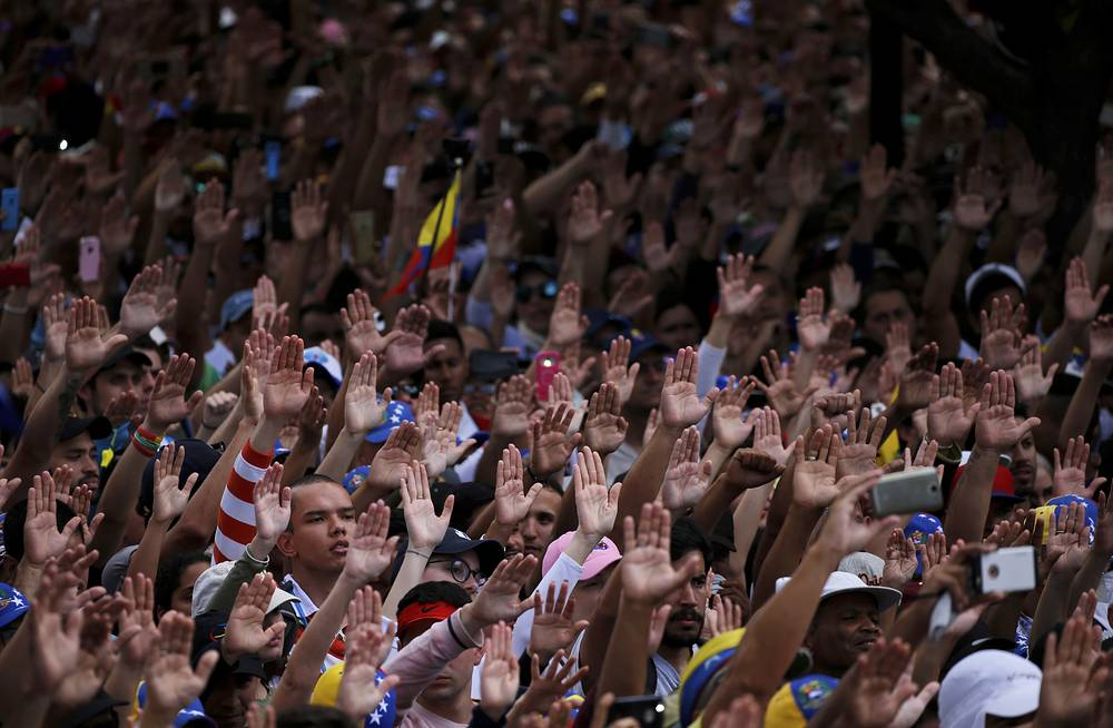 Anti-government protesters hold their hands up during the symbolic swearing-in of Juan Guaido, head of the opposition-run congress, in Caracas