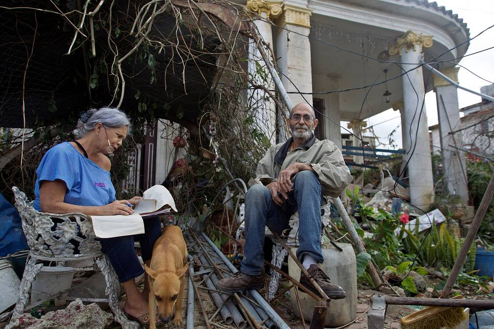 Local residents sit at the entrance of their home, partially destroyed, in Havana