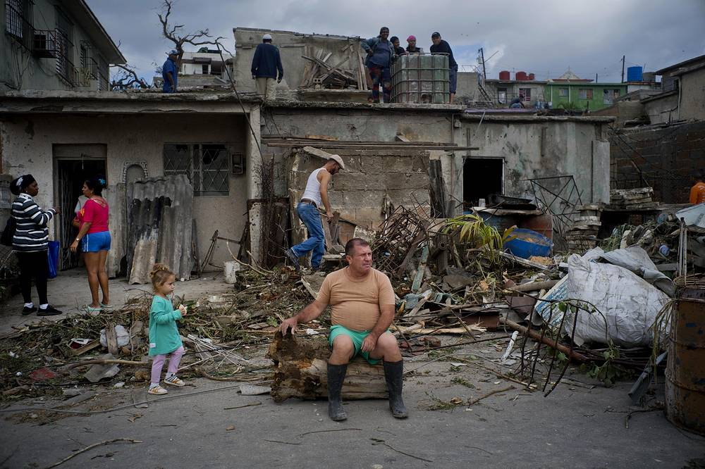 A man rests on the trunk of a tree that was toppled by a tornado after removing rubble from his home in Regla, Cuba