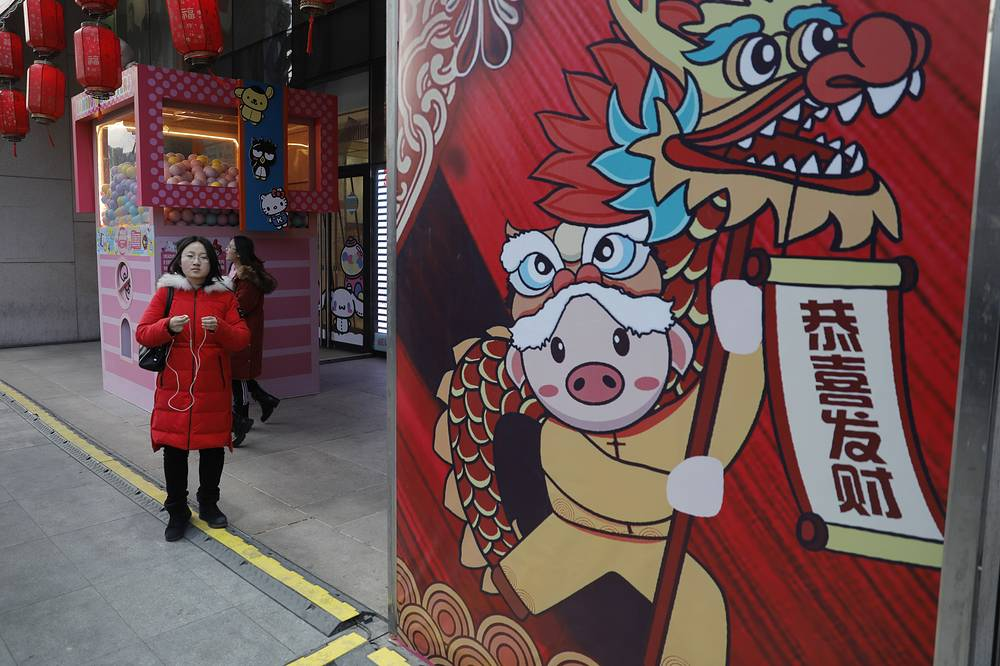 People walk past by a Spring Festival poster in Beijing, China. Lunar New Year, also named Spring Festival, will fall on February 5, 2019 and will mark the first day of the 'Year of the Pig'