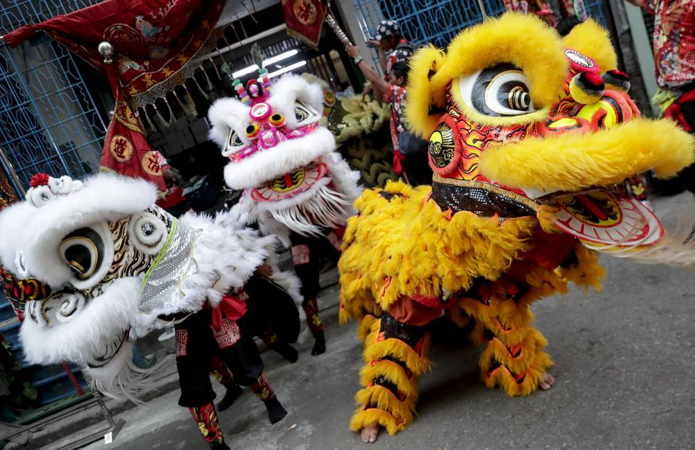 Lion dancers perform in the streets of Chinatown in Yangon, Myanmar