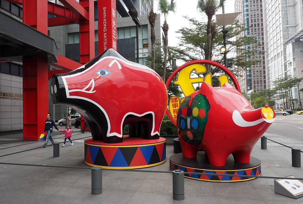 People walk past two pig scultures in Taipei, Taiwan