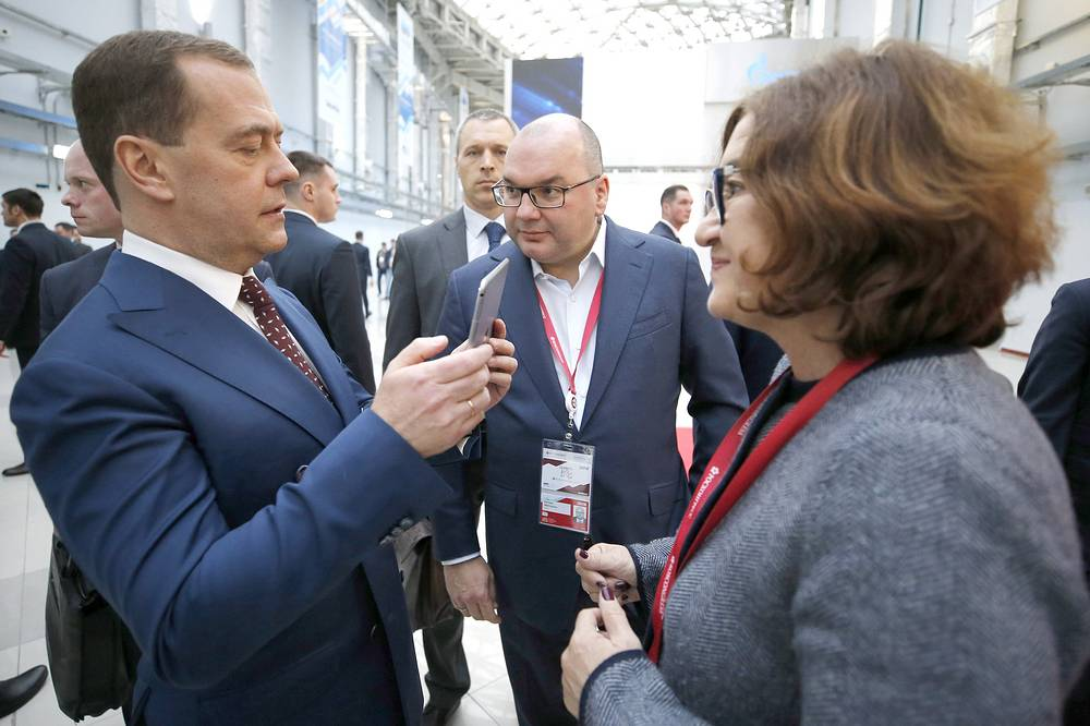 Russia's Prime Minister Dmitry Medvedev, TASS Russian News Agency General Director Sergei Mikhailov and State Tretyakov Gallery General Director Zelfira Tregulova view a virtual exhibition of Russian artist Ilya Kabakov, made by TASS, Sochi, February 14
