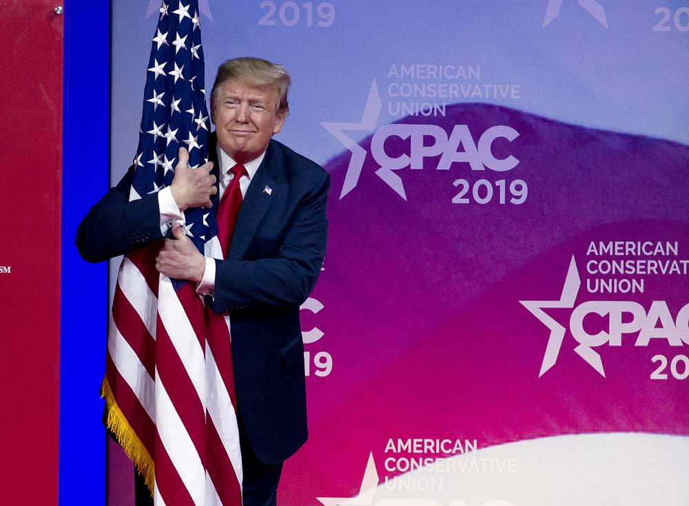 US President Donald Trump hugs the American flag as he arrives to speak at Conservative Political Action Conference, CPAC 2019, in Oxon Hill, March 2