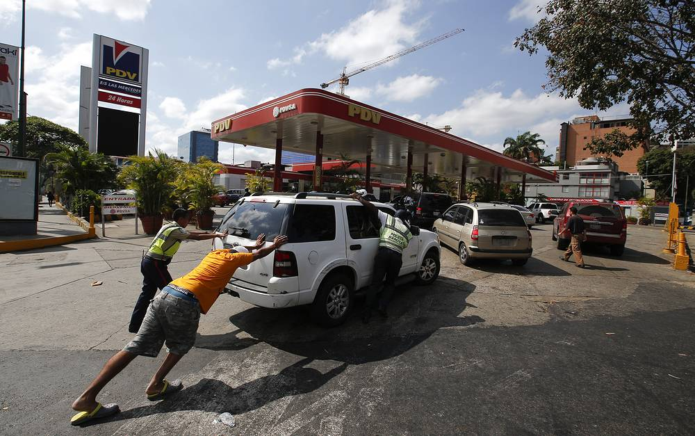 People push a car without fuel to one of the few gas stations that has its own electric generator during an electricity blackout in Caracas