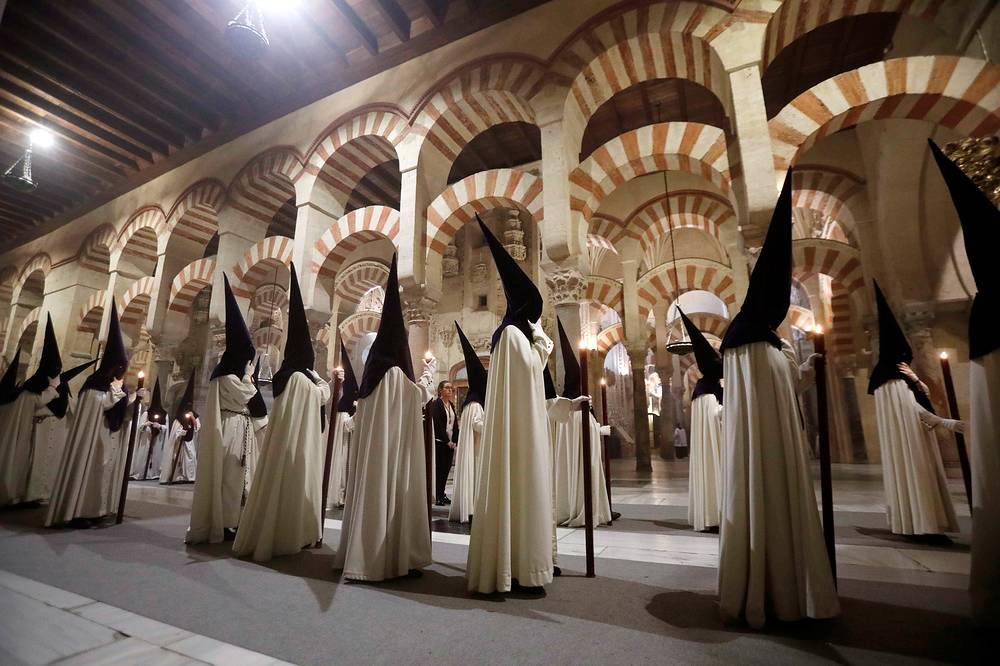 A group of 'nazarenos' or masked participants taking part in a procession inside the Mosque-Cathedral of Cordoba