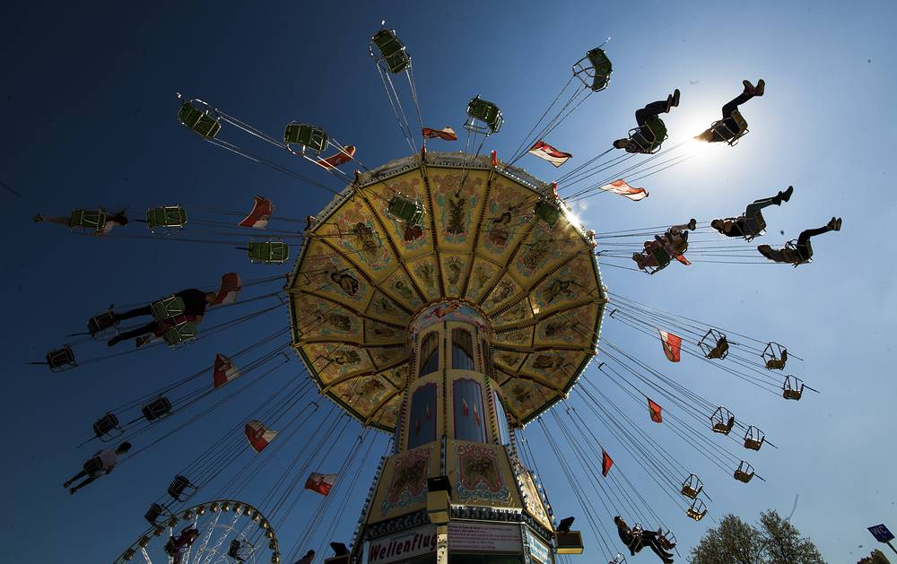People enjoying a merry-go-round at the traditional spring festival in Stuttgart, Germany, April 20
