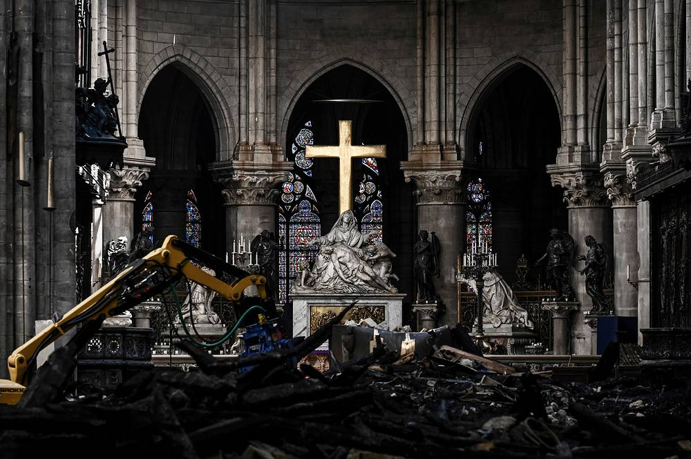 Rubble lies below the Pieta sculpture and a cross inside the Notre Dame de Paris cathedral, Paris, May 15