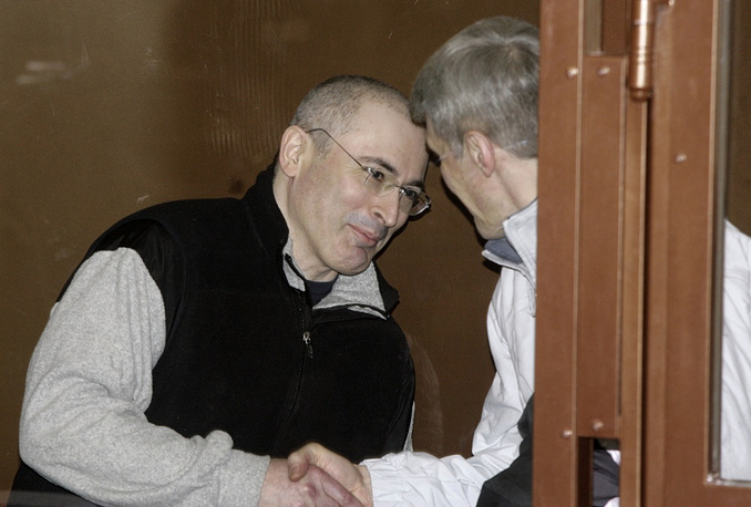 March 3, 2009. Mikhail Khodorkovsky (L) shakes hands with his partner Platon Lebedev behind bars in a courtroom in Moscow