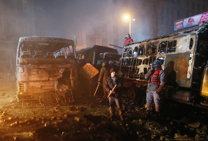 Protesters stand near burned cars as they clash with riot police during an anti-government protest in downtown Kiev