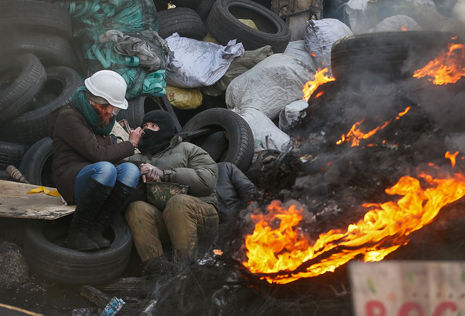 A young Ukrainian couple warms themselves near a fire at a barricade during another day of anti-government protest in Kiev