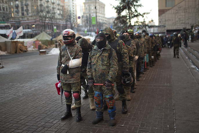Opposition supporters in military uniforms and carrying sticks as weapons, line up in front of the city council building before marching toward the parliament in Kiev on Feb. 4, 2014