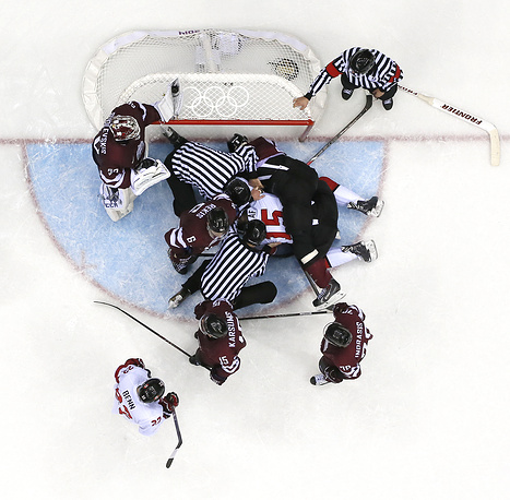 Players and referees flood the Latvia goal area during the Men's Quarterfinal match between Canada and Latvia