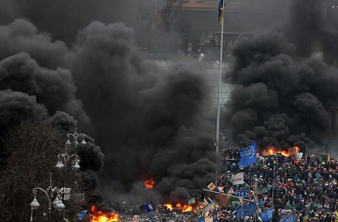Central Kiev's Independance square is filled with black smoke from burning tyres