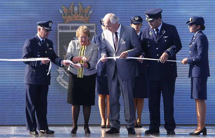Chilean President Michelle Bachelet, Chilean Minister of Defense Jorge Burgos (C) and Commander of Chilean Air Force Jorge Rojas Avila (L) cut the ribbon to start the inaugural event