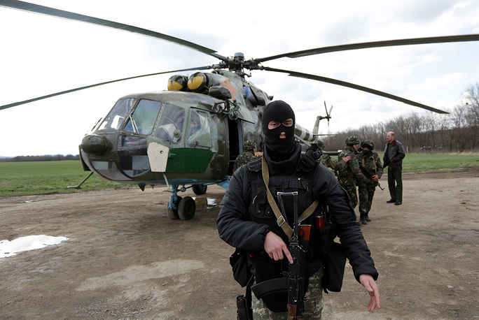 Ukrainian soldiers near a military helicopter, near Izyum city in Kharkiv Region