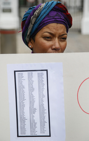 South African woman holds a poster with the names of abducted girls