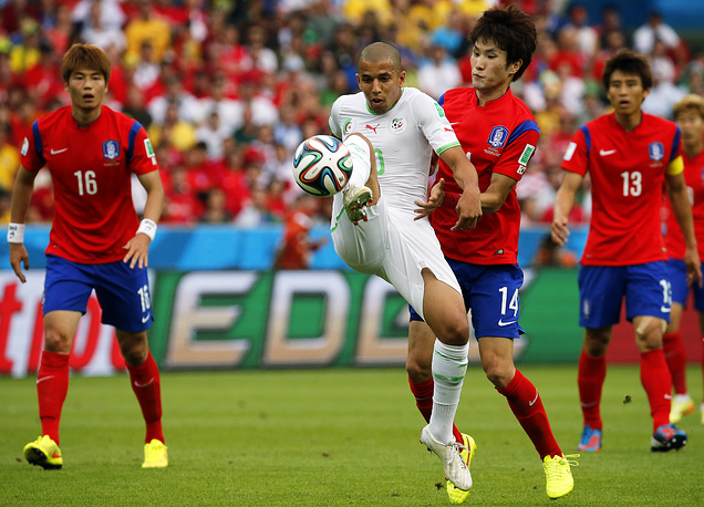Sofiane Feghouli (C) of Algeria in action against Han Kook-young (2-R) of South Korea