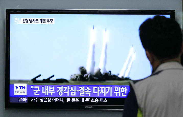 A man watches a TV news program showing the missile launch conducted by North Korea