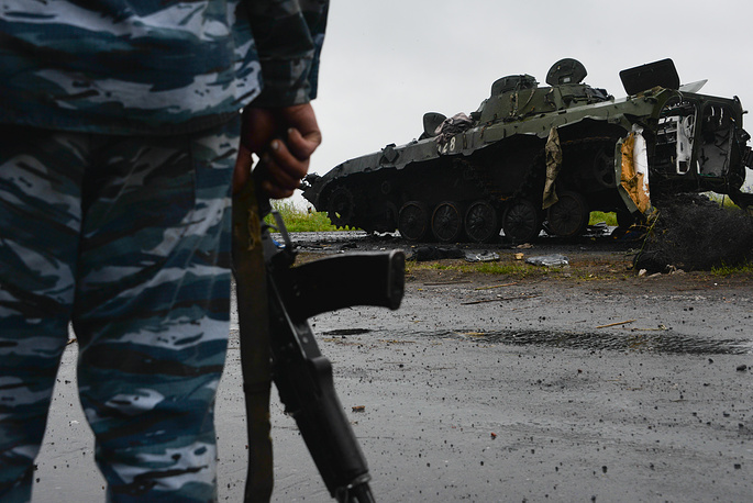 Ukrainian soldier watches a military tank